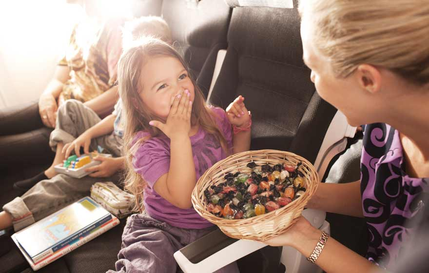 economy-skycouch-flightattendant-gives-lollies-to-children.jpg